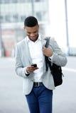 Ung man som går och ser mobiltelefonen Royaltyfria Bilder