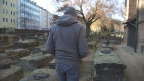 Ung man som går på den forntida kyrkogården mellan gravar, historiskt ställe, minne lager videofilmer