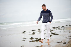 Ung man som går på stranden Arkivbilder