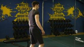 Ung man som gör övning i idrottshall arkivfilmer