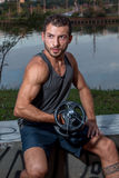 Ung man som gör bicepkrullning Fotografering för Bildbyråer