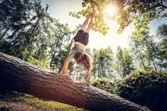 Ung man som gör en handstans på en trädstam i skogen Arkivbilder
