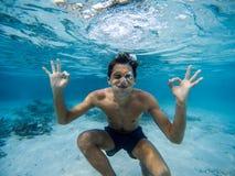 Ung man som gör grimaser undervattens- bl?tt klart vatten arkivfoto