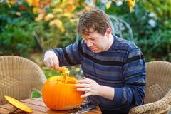 Ung man som gör halloween pumpa Arkivbild