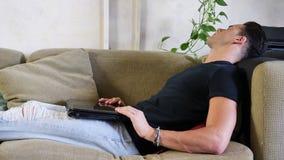 Ung man som gör läxa på bärbara datorn på soffan lager videofilmer