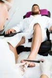 Ung man som gör pedikyr i salong pärlor för blå för begrepp för bakgrundsskönhet blir grund naturliga over för behållare kosmetis Royaltyfria Bilder