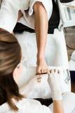 Ung man som gör pedikyr i salong pärlor för blå för begrepp för bakgrundsskönhet blir grund naturliga over för behållare kosmetis Fotografering för Bildbyråer