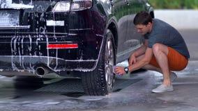 Ung man som gör ren hans svarta salongbil lager videofilmer