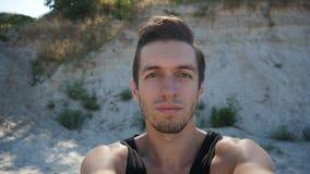 Ung man som gör selfie på stranden i sommar arkivfilmer