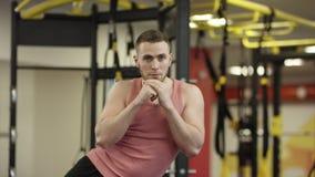 Ung man som gör sidopressövning på bänk i idrottshallen, närbild stock video