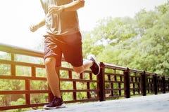 Ung man som gör sportar och att jogga som kör i en parkera fotografering för bildbyråer