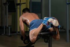 Ung man som gör tillbaka övningar i idrottshallen Royaltyfri Foto