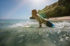 Ung man som gör vatten som surfar i havet Arkivfoton