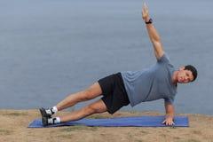 Ung man som gör yoga utanför i naturlig miljö Arkivbild