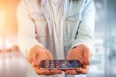 Ung man som ger en tom hand med smartphonen på kontoret Royaltyfria Bilder