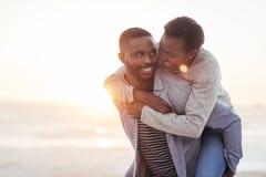 Ung man som ger hans flickvän en ridtur på axlarna på stranden royaltyfri foto