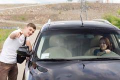 Ung man som ger riktningar till en kvinnachaufför Arkivbild