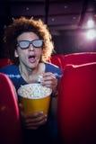 Ung man som håller ögonen på en film 3d och äter popcorn Royaltyfria Bilder
