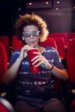 Ung man som håller ögonen på en film 3d och dricker sodavatten Arkivbild