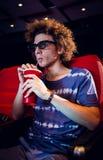 Ung man som håller ögonen på en film 3d och dricker sodavatten Arkivfoto