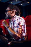 Ung man som håller ögonen på en film 3d och dricker sodavatten Royaltyfri Bild