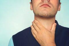 Ung man som har den öm halsen och trycker på hans hals som bär en lös t-skjorta mot ljus - blå bakgrund hård svala till nodul arkivbilder