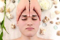 Ung man som har den head massagen i brunnsortsalongen Arkivfoton
