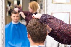 Ung man som har hår att klippas av salongstylisten arkivbild