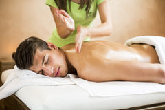 Ung man som har massage i brunnsort arkivbild