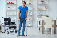 Ung man som hemma återställer efter kirurgi med kryckor och en w Royaltyfria Bilder