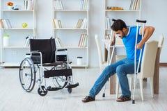 Ung man som hemma återställer efter kirurgi med kryckor och en w Arkivfoton