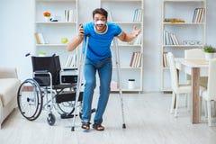 Ung man som hemma återställer efter kirurgi med kryckor och en w Royaltyfri Foto