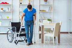 Ung man som hemma återställer efter kirurgi med kryckor och en w Royaltyfri Bild