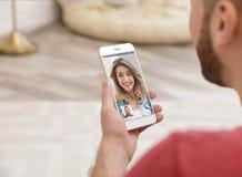 Ung man som hemma anv?nder video pratstund p? smartphonen Utrymme f?r design royaltyfria bilder