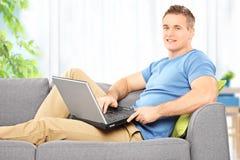 Ung man som hemma placerar på en soffa med bärbara datorn royaltyfria bilder