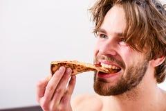 Ung man som hemma vilar med en nakenstudie och en pizza Shirtless stilig ung man med pizza på säng Banta, vem att bry sig omkring royaltyfria foton