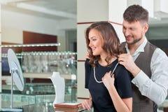 Ung man som hjälper hans flickvän med den passande halsbandet på jen arkivfoton