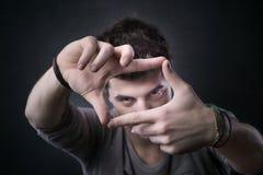 Ung man som inramar hans ögon med fingrar royaltyfri foto