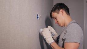Ung man som installerar strömbrytaren arkivfilmer