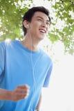 Ung man som joggar, medan lyssna till musik Royaltyfria Bilder