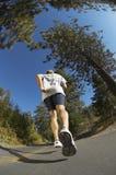 Ung man som joggar på vägen Arkivbild