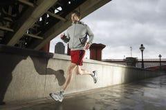 Ung man som joggar på stormig dag Arkivfoton