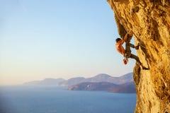 Ung man som kämpar för att klättra den utmanande rutten på klippan Arkivfoto