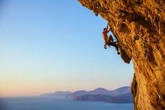 Ung man som kämpar för att klättra den utmanande rutten på klippan på solar Royaltyfria Foton