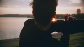 ung man som 4K sträcker armar nära en soluppgångsjö tillbaka sikt Färdig idrottsman för man som värmer upp nära härlig stilla sik stock video