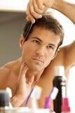 Ung man som kammar hans hår Arkivfoto