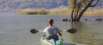 Ung man som kayaking p? sj?n royaltyfri foto