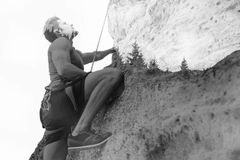 Ung man som klättrar en brant vägg i berg royaltyfria foton