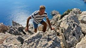 Ung man som klättrar till överkanten av en hög klippa arkivfilmer