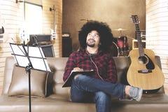 Ung man som komponerar en sång i musikstudio Royaltyfri Fotografi